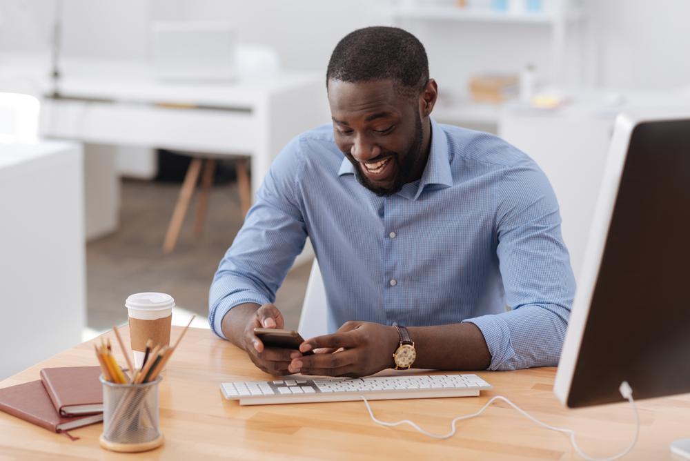 Man smiling at his phone.