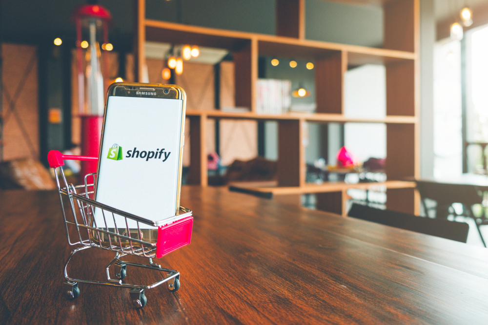 Smartphone inside of a shopping cart with the Shopify logo on it's display.