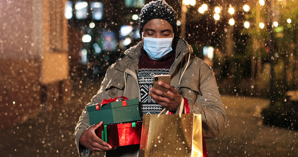 Man carrying holiday gifts.