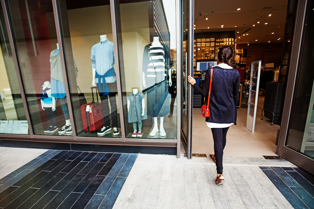 Woman entering retail shop.