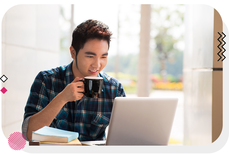Man drinking coffee while working from his laptop.